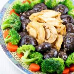 Braised Mushrooms and Abalone surrounded by blanched broccoli florets and carrot coins.