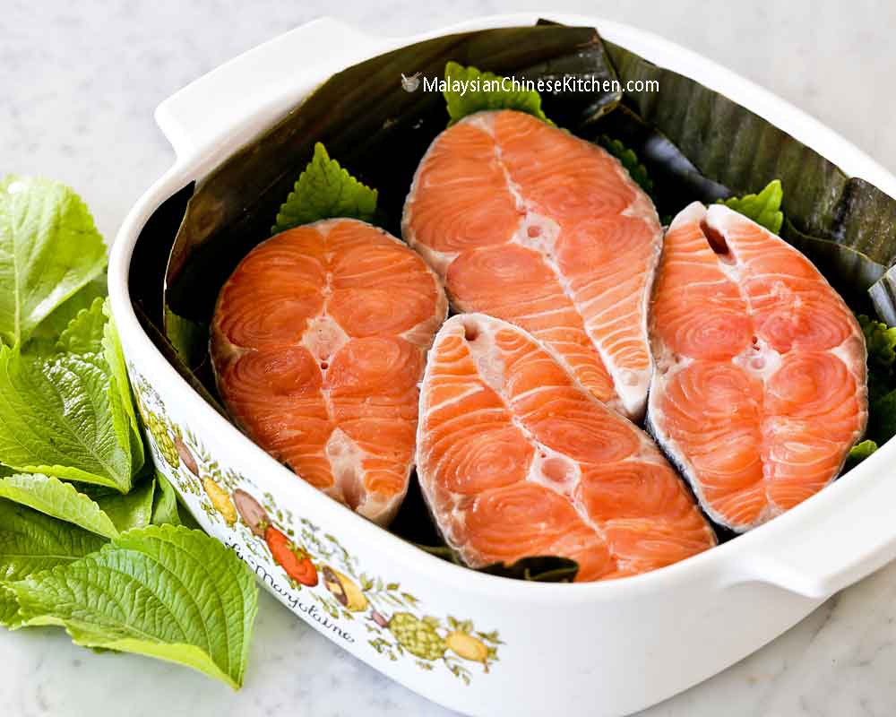 Salmon steaks arranged in banana leaf lined casserole dish used in this recipe.