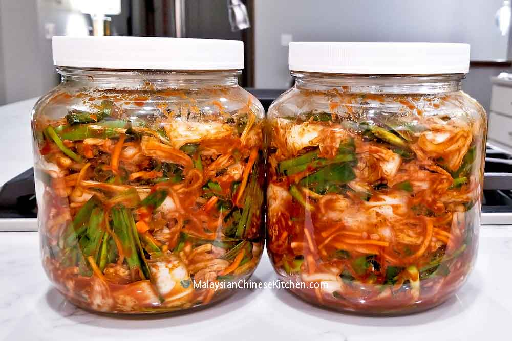 Two containers of  freshly made Napa Cabbage and Scallion Kimchi.