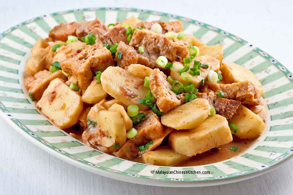 Delicious Braised Ngaku Arrowheads with Roast Pork Belly sprinkled with sliced green onions.
