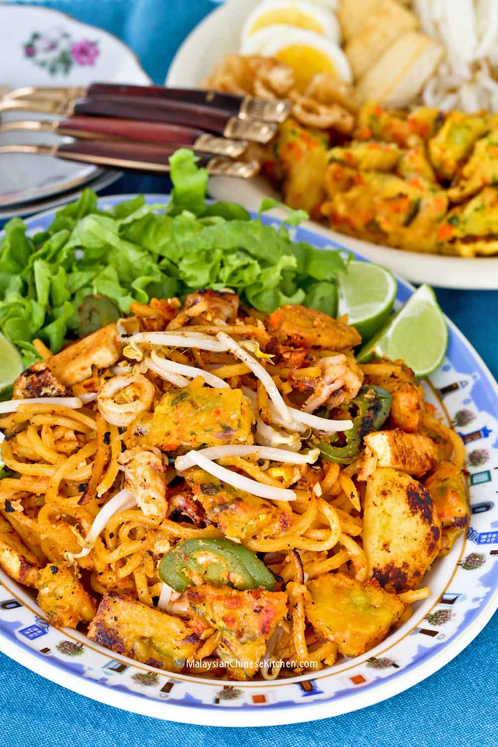 Mee Goreng Mamak served with shredded lettuce and lime wedges.